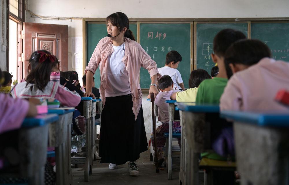 疼得厉害时,她跪在板凳上给孩子们讲课